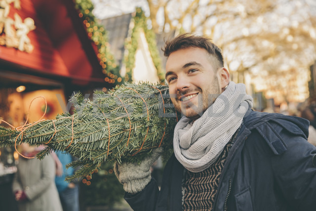 Smiling man with a wrapped-up tree walking over the Christmas Market - MFF002652 - Mareen Fischinger/Westend61