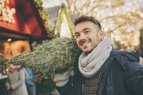 Smiling man with a wrapped-up tree walking over the Christmas Market - MFF002652