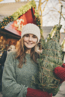 Smiling woman with a wrapped-up tree standing on the Christmas Market - MFF002655
