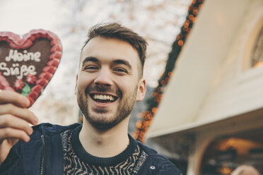 Portrait of man holding up a gingerbread heart on the Christmas Market - MFF002670