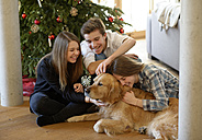 Three young friends cuddling with Golden Retriever on the floor of living room at Christmas time - LBF001374