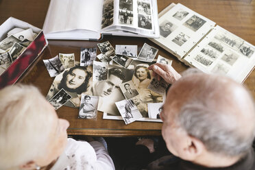 Senior couple with photo albums and old photographies at home - GEMF000718