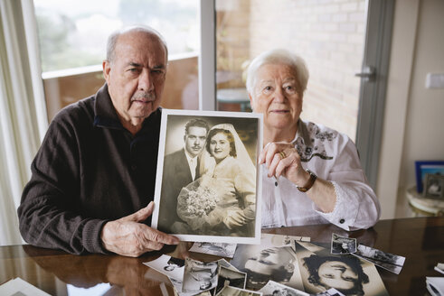 Senior couple showing their wedding photo at home - GEMF000721