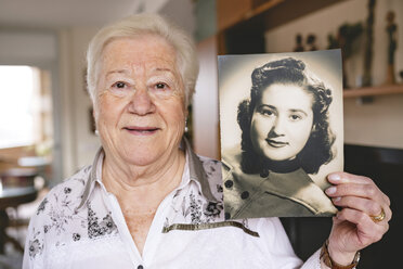 Portrait of senior woman showing an old picture of herself - GEMF000724
