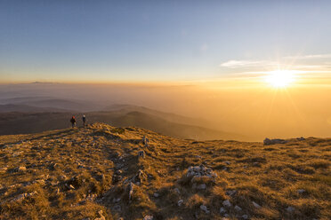 Italy, Marche, Monte San Vicino, two hikers looking at view at sunset - LOMF000211