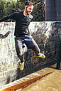 Participant in extreme obstacle race jumping over wall - MGOF001379