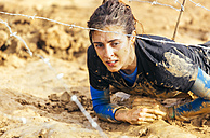 Participant in extreme obstacle race crawling under barbed wire - MGOF001385