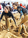 Participants in extreme obstacle race, running through mud - MGOF001388