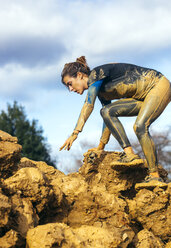 Participants in extreme obstacle race, running through mud - MGOF001391