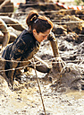Participant in extreme obstacle race crawling under barbed wire - MGOF001394