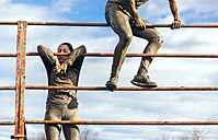 Participants in extreme obstacle race climbing over hurdle - MGOF001403