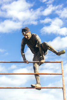 Participants in extreme obstacle race climbing over hurdle - MGOF001406