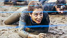 Participants in extreme obstacle race crawling under electric wire - MGOF001412