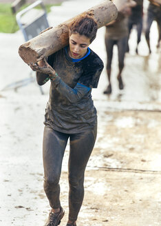 Participant in extreme obstacle race carrying tree trunk - MGOF001415
