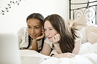 Two teenage girls lying on bed looking at laptop - OJF000091