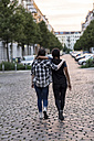 Two teenage girls walking on a street arm in arm - OJF000115