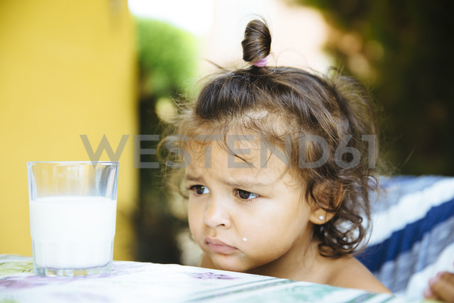 Portrait of unhappy little girl with glass of milk - ERLF000129