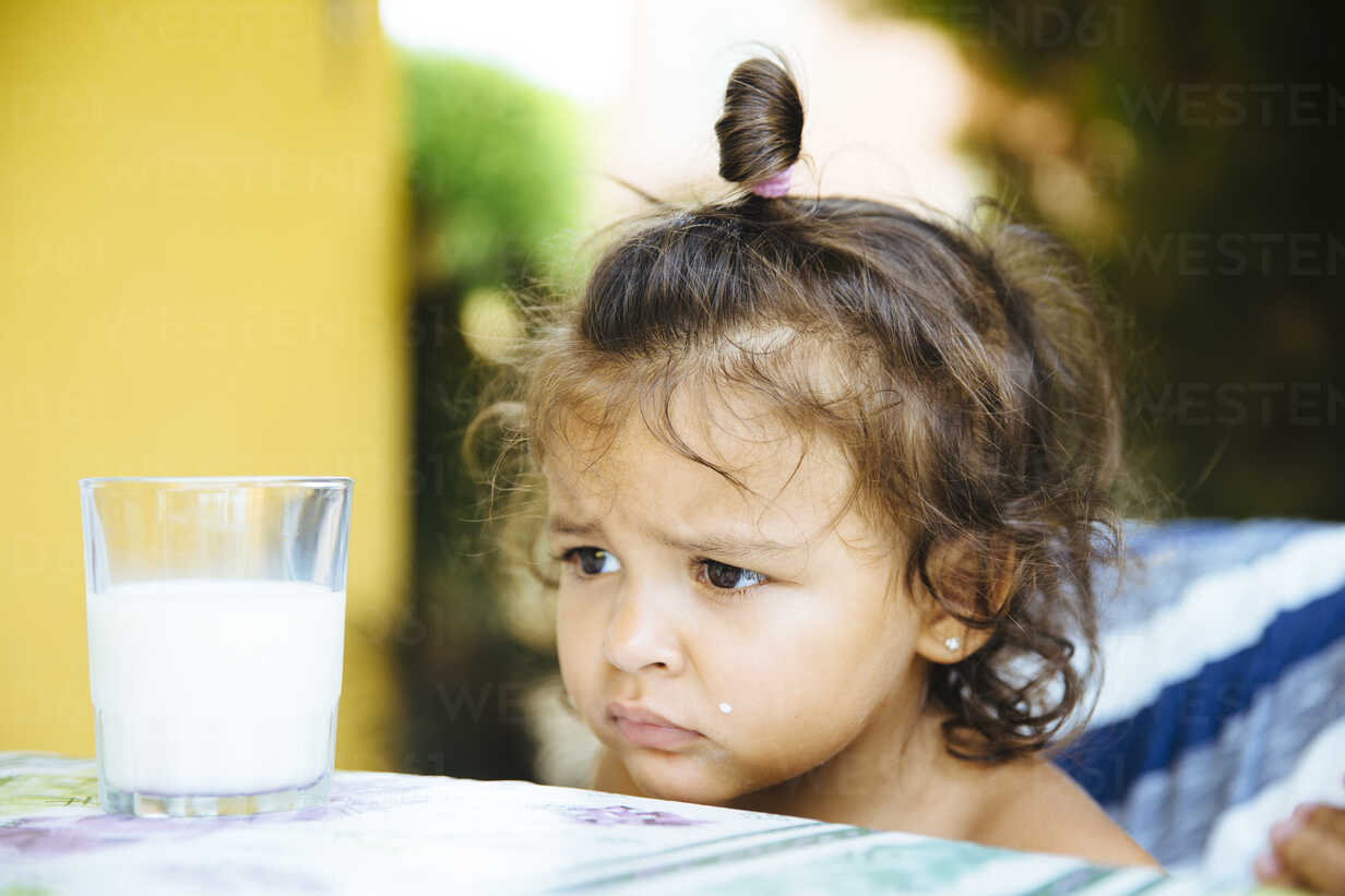 Portrait of unhappy little girl with glass of milk - ERLF000129 - Enrique Ramos/Westend61