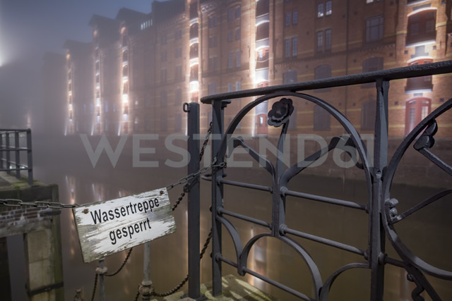 Germany, Hamburg, Closed stairway in the Historic Warehouse district Speicherstadt in fog at night - NKF000457