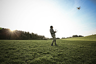 Man on a meadow flying drone - REAF000025