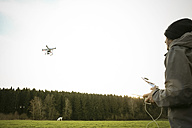 Man on a meadow flying drone - REAF000031
