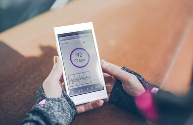 Mid adult woman using heatr rate monitor app on smart phone - DAPF000026