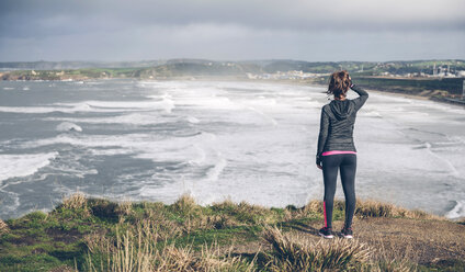 Sporty mid adult woman on cliff looking at sea - DAPF000041