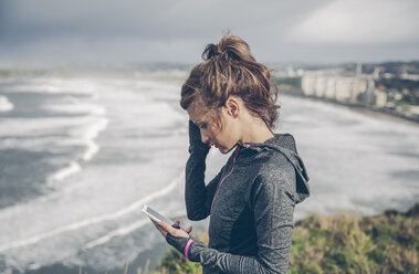 Portrait of mid adult sportive woman using smart phone - DAPF000044