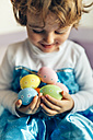 Happy little girl holding Easter eggs - MGOF001422