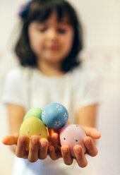 Girl's hands holding painted Easter eggs - MGOF001425