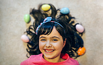 Portrait of happy little girl with Easter eggs - MGOF001428