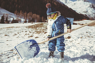 Italy, Val Venosta, Slingia, small boy using a large snow shovel - MFF002710