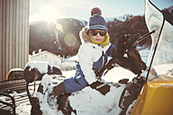 Italy, Val Venosta, Slingia, boy with sunglasses sitting on a snowmobile - MFF002713