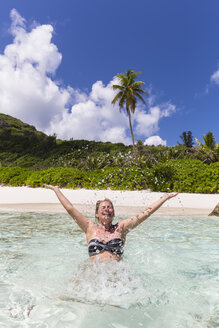 Seychelles, Anse Cocos, female tourist in water - FOF008420