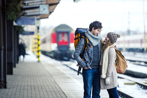 Smiling young couple on station platform - HAPF000200