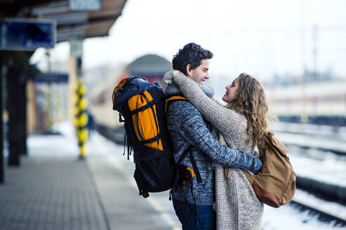 Smiling young couple embracing on station platform - HAPF000203