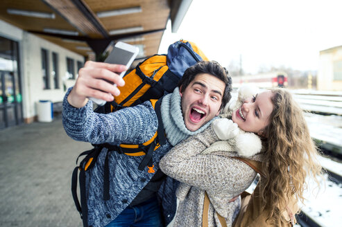 Playful young couple on station platform taking a selfie - HAPF000206