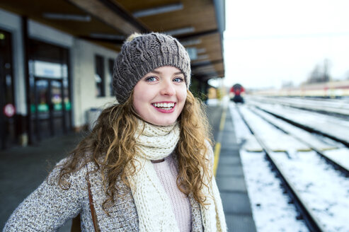 Portrait of smiling teenage girl on station platform - HAPF000209