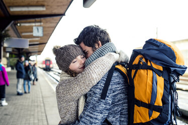 Smiling young couple embracing on station platform - HAPF000212