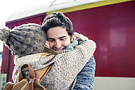 Happy young couple embracing in front of train - HAPF000215
