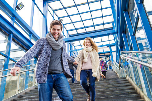 Young couple in a hurry running downstairs at train station - HAPF000224