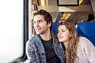 Smiling young couple in train car looking out of window - HAPF000227