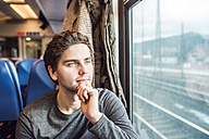 Young man in train car looking out of window - HAPF000230