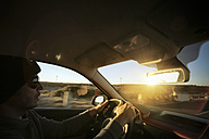 Portugal, Madeira, man driving car at sunset - REAF000047