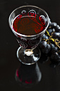 Glass of red wine and blue grapes on black ground - SARF002544
