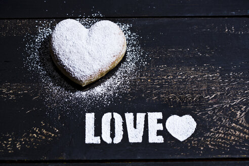 The word 'Love' stenciled with icing sugar and a heart-shaped cruller on dark wood - MAEF011279