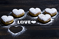 The word 'Love' stenciled with icing sugar and five heart-shaped crullers on dark wood - MAEF011282