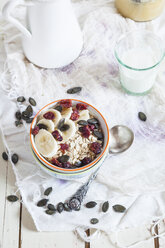 Bowl of oat flakes with dried cranberries, banana slices and pumpkin seed - SBDF002691