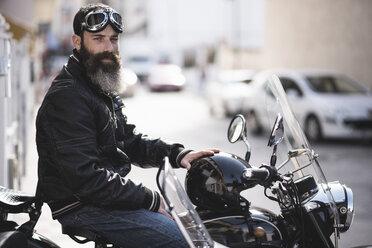 Spain, Jaen, portrait of bearded biker sitting on his sidecar motorcycle - JASF000393