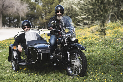 Portrait of two bikers standing with their sidecar motorcycle on a meadow - JASF000396